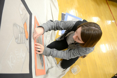 Lewisburg High School junior Chloe Auman, 16, pins up artwork Wednesday morning as she helps to set up for the district's art show opening tonight at 6:30 at the Lewisburg Middle School gymnasium.