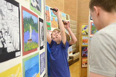 Lewisburg Middle School students Dawson Aikey, 14, left, and Justin Gessner, 13, set up boards with artwork on them Wednesday morning for the opening of the district art show tonight at 6:30 at the Lewisburg Middle School gymnasium.