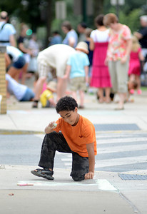 Jonathan Phelps, 11, of Lewisburg adds color to his chalk art as participants line Market Streein during Lewisburg's Sidewalk Chalk Street Festival Friday July 13, 2012.