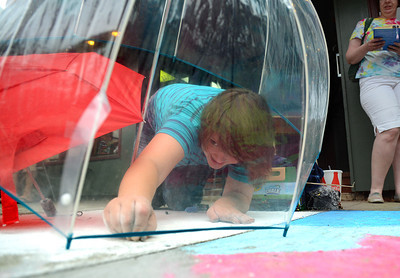 Megan McGinnis, 14, of Lewisburg reaches to add details to her art piece protected from the threat of bad weather during Lewisburg's Sidewalk Chalk Street Festival Friday July 13, 2012.