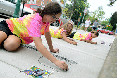 Saige Graham, 12, from left, Kacee Reitz, 11, and Taryn Chubb, 12, all of Milton start on the outlines for their art creations during Lewisburg's Sidewalk Chalk Street Festival Friday July 13, 2012.