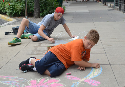 Brent Schreffler, left, of Lewisburg and one of his sons, Brayden, 8, work on filling their sidewalk square during Lewisburg's Sidewalk Chalk Street Festival Friday July 13, 2012.