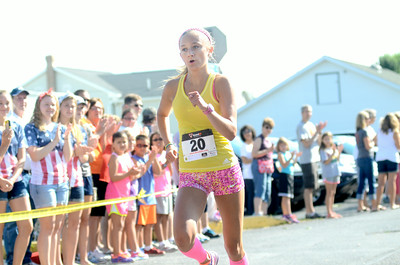 Allison Billas of Danville sprints across the finish line at Friday's Mifflinburg 5k to take first place overall in the women's half of the race.