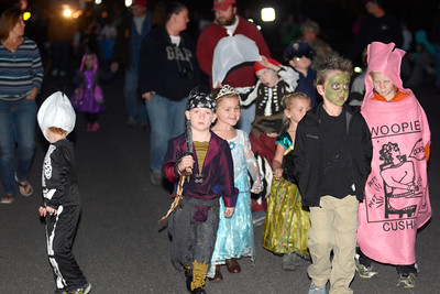 A group of kids dressed up in their Halloween costumes walk along in the Mifflinburg Halloween Parade on Monday night.