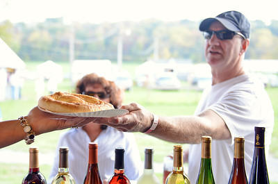 Tony and Kathy Darpino, of Lewisburg, recieve a pretzel from Paula Christy, of Mifflinburg, at Mifflinburg's Oktoberfest on Friday afternoon on Route 45.