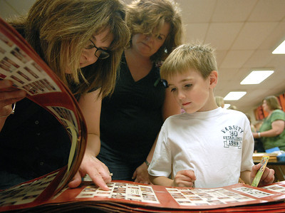 First-grade student, Ian Neiswender, 7, looks for family members though decades of school photos with his mom, Crystal, left, and his teacher Mrs. Beck during New Berlin Elementary's open house Thursday May 18, 2012.