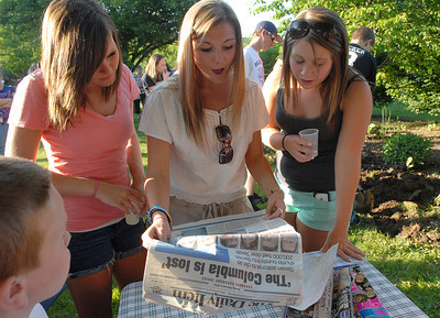 Mifflinburg seniors, Val Keister, from left, Kate Erb, and Hannah Shultz react to seeing the news from the day in 2003 when they buried with classmates at New Berlin Elementary School.  Students gathered with family and friends during the open house Thursday May 17, 2012 to relive memories and celebrate their school.