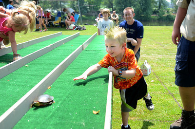 Michael Snook II encourages his turtle Speedy on as his father Michael Snook, Lewisburg, watches on during Wednesday's Turtle Derby in New Berlin.