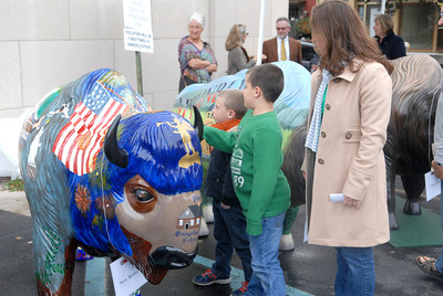Darren Yoder, 6, left, and his brother Jayden Yoder, 8, and mother Wendy Yoder, check out the New Berlin painted buffalo on Wednesday as part of the Union County Bicentennial celebration.