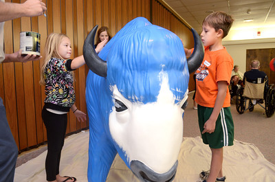 Lewisburg Elementary third grade students Jasmine Smith, left, and Thomas Hess, both help paint the Kelly Township buffalo at Riverwoods on Wednesday morning.