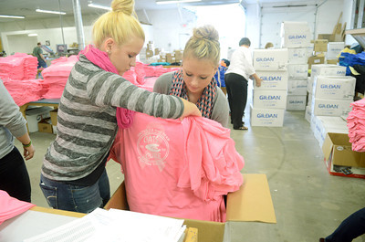 Mifflinburg High School cheerleaders Katelinn Gillespie, 16, left, and Katelyn Sheesley, 16, box up pink t-shirts on Monday at Green Ridge Graphics that they sold to raise money to fight cancer.