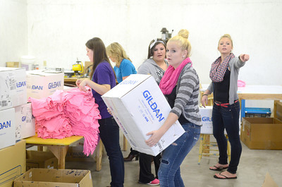 Katelinn Gillespie, 16, carries a box of pink t-shirts while she and fellow Mifflinburg High School cheerleaders Katie Heimbach, 16, left, Chelsea Snook, 17, and Katelyn Sheesley, 16, right, load up t-shirts that they sold to raise money to help fight cancer.