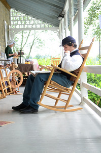 Dakota Kelley of Middleburg sits in a rocking chair on the porch of the Dale Engle Walker House in Lewisburg on Wednesday as part of the Rural Heritage Days.
