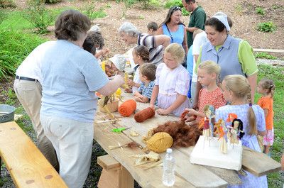 A group of kids and adults gather around the table to make corn husk dolls at the Rural Heritage Days on Wednesday at the Dale Engle Walker House.
