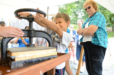 Tommy Aversa, 8, Cogan Station, turns the wheel on a press to squeeze the water out of a piece of hand made paper at the Rural Heritage Days in Lewisburg at the Dale Engle Walker House.