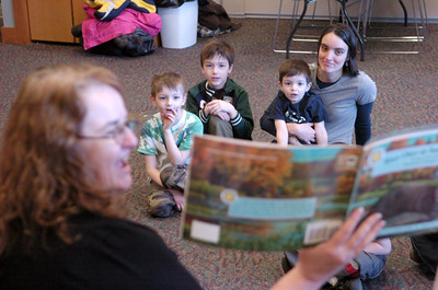 Mende Croll, left, reads a story about otters at the Union County Library as Joel Langdon, 5, and his brothers Ephraim, 7, and Caleb, 3, and his mother Megan Langdon, listen on Friday afternoon.