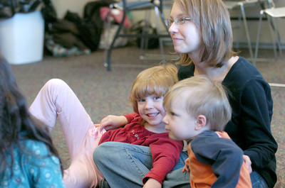 Erin DeSantis, 5, lays on her mother, Liz DeSantis, next to her brother Daniel DeSantis, 2, as they listen to a story at the Union County Library.