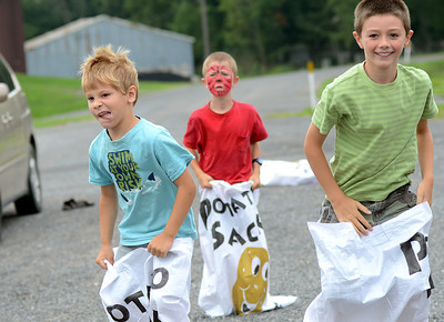 Simon Snook, 5, from left, Bryant Groff, 6, and Jonah Harvey, 8, race for the finish line in one of the potato sack races Tuesday Aug. 14, 2012 during West End Library's carnival to celebrate their summer reading program.  Families gathered at the library in Laurelton for games and food and to redeam coins they earned by reading throughout the summer.