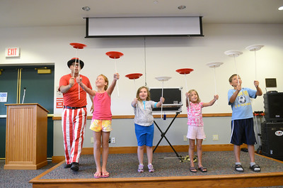 Paul Miller of the Flow Circus, left, puts the last plate onto the pole held by Autumn Shahan, 6, Delaware, along side other helpers Jailyn Smith, 6, Milton, Kelsey Shahan, 6, Delaware, and K.J. Shahan, 9, Delaware, during The Science of Awesome show at the Union County Library on Friday.