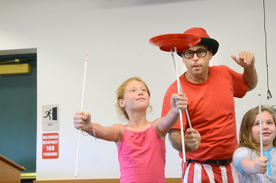 Paul Miller places a spinning plate onto a pole held by Autumn Shahan, 10, Delaware on Friday at the Union County Library during The Science of Awesome show.