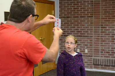 Paul Miller of the Flow Circus performs a magic trick for Katie Kelley, 8, Lewisburg, during his Science of Awesome program at the Union County Library on Friday afternoon.