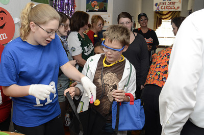 Jenny Williams, left, of the Greater Susquehana Valley Chamber of Commerce, passes a piece of candy to Milton Elementary Life Skills student Austin Gehrer, 11, at the Trail of Treats on Wednesday at the Lewisburg Best Western Hotel.