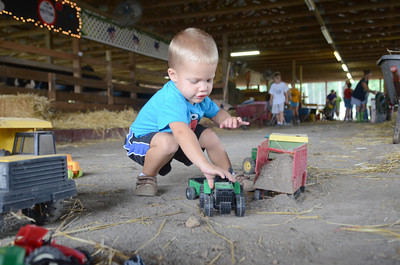 Joel Gessner, 2, Lewisburg, plays with his tractors in one of the animal barns at the West End Fair on Monday morning.