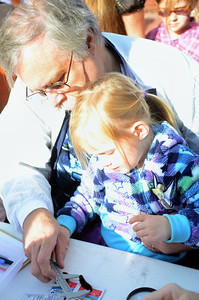Steve Connelley helps his granddaughter Keira Parker, 3, both of Lewisburg, measure a woolly worm during the judging of the woolly worms at the Woolly Worm festival on Saturday afternoon at Hufnagle Park. The judges decided that it was going to be a harsh winter.