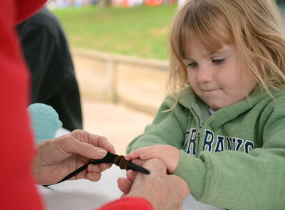 Julia Opperman, 4 of Lewisburg, is helped by Nada Gray, of Lewisburg, to make a woolly worm out of pipe cleaners at the Woolly Worm Festival at Hufnagle Park in Lewisburg on Saturday afternoon.