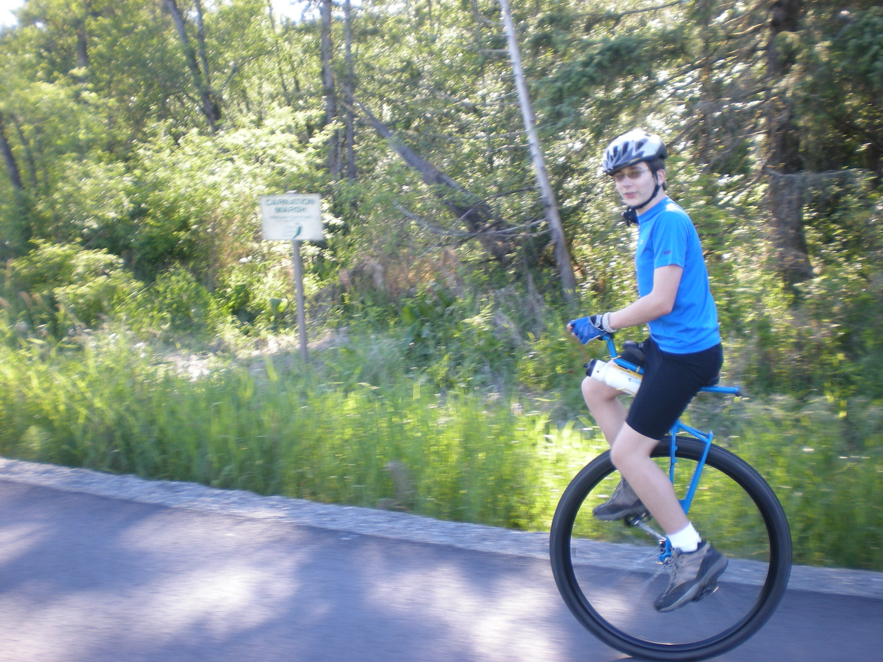 2008: Miles riding past the Carnation Marsh sign. This time a month ago, the road he is riding on was submerged under the Snoqualmie River. Nicer conditions today.