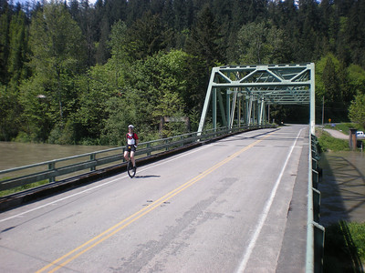 Jeff crossing the Snoqualmie River.  Note how high the river is, due to two days of very high temperatures applied to record snowfall about 45 miles upstream from here. The height of the river would become a factor about 10 miles further along in our ride.