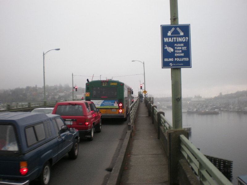 """Cars, trucks, and unicycles pile up waiting for the Ballard Bridge drawbridge to come back down so we can pass. The sign says """"Idling Pollutes"""", but not the sort of idling we were doing."""