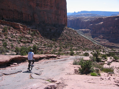 A. Rider dropping down from the Moab Rim Trail.