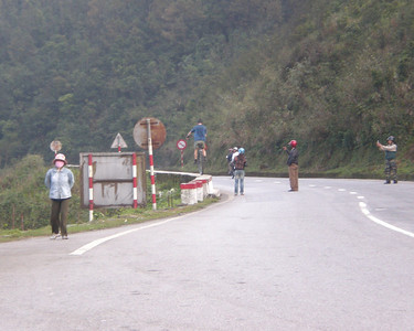 Top of Hai Van Pass. Corbin (USA) entertains the locals by riding his 36-er down the skinny guard-wall at the side of the road. He rode it all the way down to the end, which is behind the left-most lady with the pink mask's head.