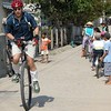 Me riding through a narrow village street. Kids focusing on the downed unicyclist right behind me. Photo: G. Huntley