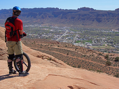 Michael Grant looks down upon the town of Moab from the backside of the Slickrock Trail. The trail is high above the town!
