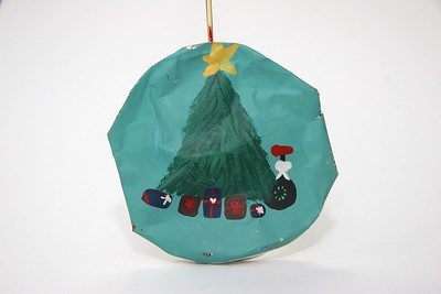 Hand-painted crushed soda can ornament with a unicycle under the Christmas tree. Artist: Melanie Bazile.