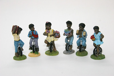 "Black kids on unicycles, plastic, about 2.5"" high"
