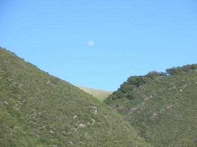 The moon, showing above a gap in Mt. Diablo.