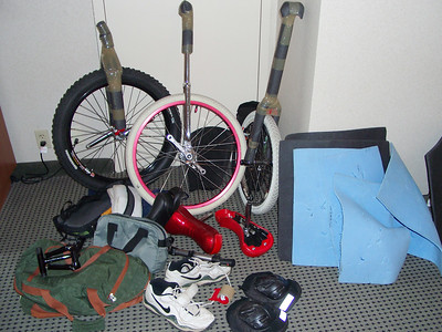 "The complete contents of the unicycle bag for this trip to NAUCC. 24 x 3"" MUni, 24"" regular uni, 20"" Freestyle uni with very long frame (which I left on), Camelbak, rain jacket, leg armor, two sets of kneepads, saddles, my foam panels, pump, gray bag of tools, Coker extension handle, riding shoes, extra tape, and green bag containing gloves, pedals and maybe more! I think this collection of stuff came out to more than the 50 pounds that's now the striclty-enforced maximum on US carriers. At that time, it only cost $25 extra for being overweight...  Don't be overweight these days, it can be very expensive! Always weigh your luggage before leaving home."