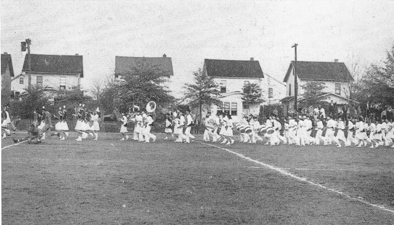 The 1941-42 Union High School Marching Band marches on the old Union High school Football Field with Berwyn St. in the background.