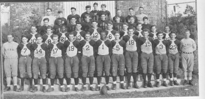 "1932 UHS football team features Eulace ""Euley"" Peacock wearing #1 and quarterback John ""Gus"" Ghuzzi."