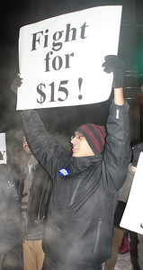 This Jobs With Justice supporter joins a protest for higher wages for fast food workers, in the frigid early morning hours, outsde a Denver area McDonalds.