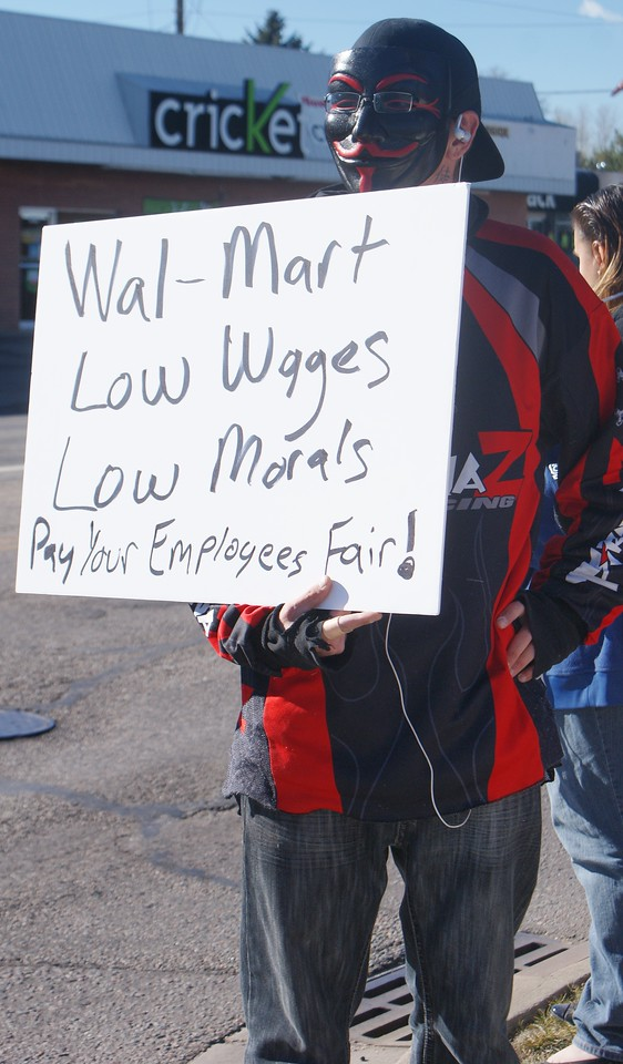 """Black Friday protester, wearing an """"annonymous"""" mask, objects to Walmart's low wages."""