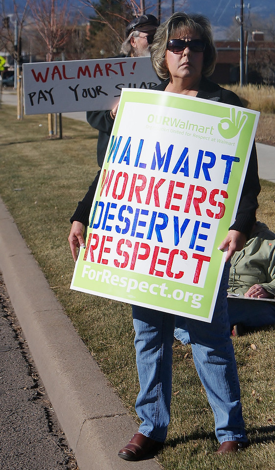 Protesters from unions and community groups line the street outside a Walmart in suburban Denver, to demonstrate against the companies low wages and mistreatment of their workers.