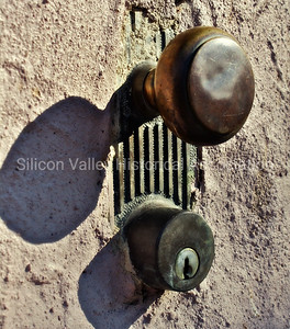Rustic metal doorknob and lock cemented into a wall in Bisbee, Arizona