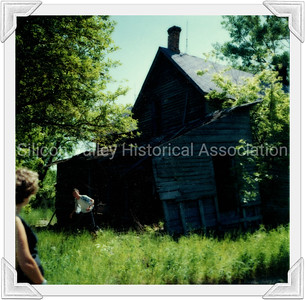 Two people touring a dilapidated house in Standish, Michigan in 1972