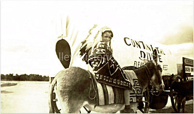 Boy on a burro by a covered wagon at the Continental Divide in 1940