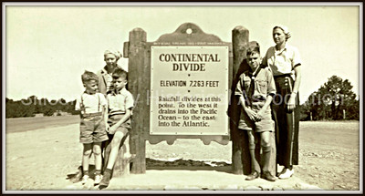 Family standing by the Continental Divide Elevation 7,253 Feet sign in 1940