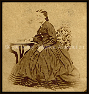 1860 cartes de visite photograph of a young woman sitting at a table in a Victorian style dress